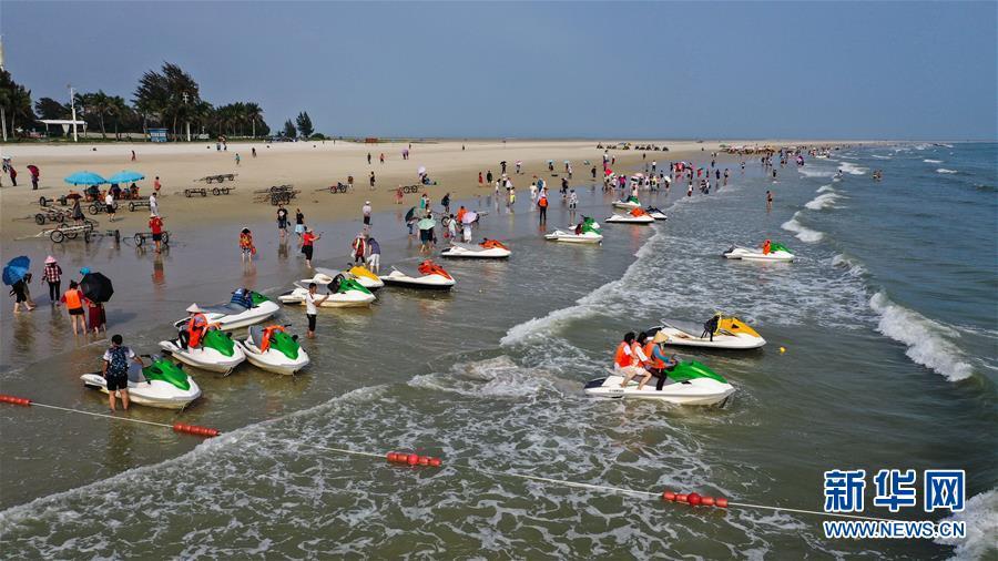 4月18日,游客在北海银滩游玩。 近日,随着气温回升,众多游客来到广西北海银滩旅游,享受碧海蓝天带来的乐趣。 <br/>