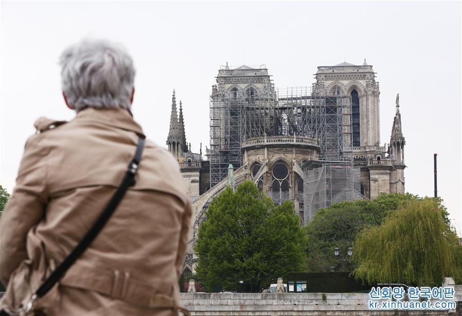 4월 16일, 프랑스 파리, 한 노부인이 세느강 강변에서 &lsquo;상처 입은&rsquo; 파리 노트르담 대성당을 바라보고 있다. 현지시간 15일 18시 경, 파리 노트르담에 갑자기 화재가 일어나 정상과 타워 꼭대기가 타버렸고 다행히 건물 메인 부분은 보존되었다. 16일 이른 아침, 상처 입은 이 &lsquo;옛친구&rsquo;를 보러 군중들이 끊임없이 파리 노트르담으로 몰려들었다. 어떤 사람은 꽃을 가져와 세느강 제방에 놓았고 대부분 사람은 강변에 서서 멀지 않은 곳의 노트르담 대성당을 묵묵히 지켜보았다. [촬영/ 신화사 기자 가오징(高靜)]<br/>