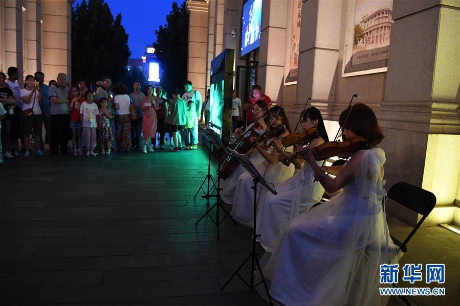 <br/>   6月9日,在天津市五大道夜间经济示范街区,学生在为市民表演。新华社记者 马平 摄<br/>