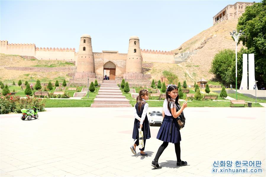 6월12일, 타지키스탄 수도 두샨베 이서의 히소르(Hisor)에서 학생 두 명이 히소르성 앞을 지나가고 있다. 구워서 말린 적벽돌로 쌓은 히소르성은 타지키스탄 수도 두샨베 이서 약25km에 자리하고 있으며, 3000여년의 역사를 자랑한다. 소련과학원과 타지키스탄대 학자의 고증에 의하면 장건이 대완에서 귀국할 때 이곳을 지나면서 중앙아시아 중심 대완, 대하, 소그드 지역의 자료를 수집해 후세가 실크로드의 번성을 실증하는 데 중요한 지리적 정보를 제공했다고 한다. [촬영/신화사 기자 사다티(沙達提)]<br/>