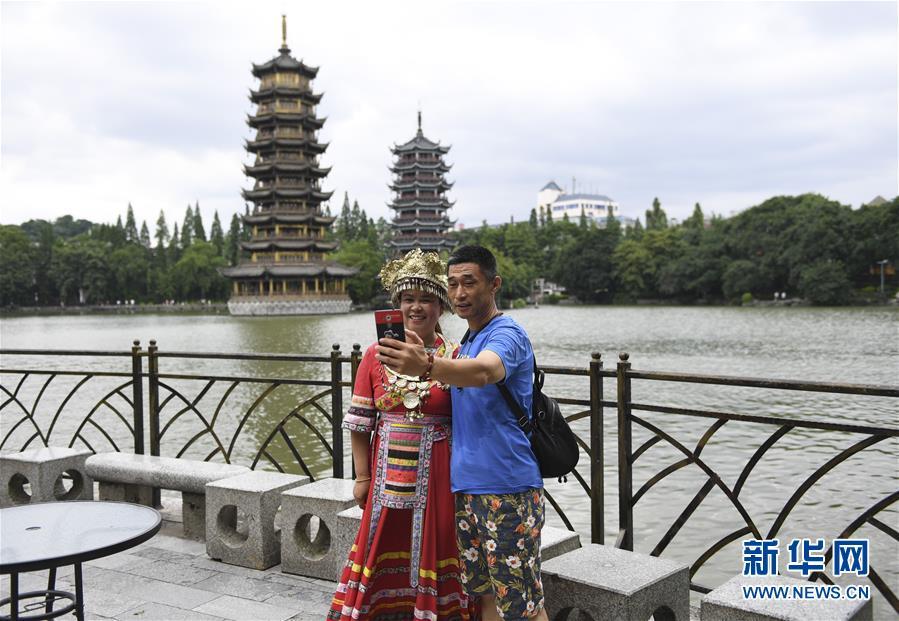 <br/>  6月13日,游客在桂林日月双塔景区拍照留念。 当日,广西桂林连日阴雨天气暂停,吸引不少游客前来旅游观光。 新华社记者 曹祎铭 摄<br/>