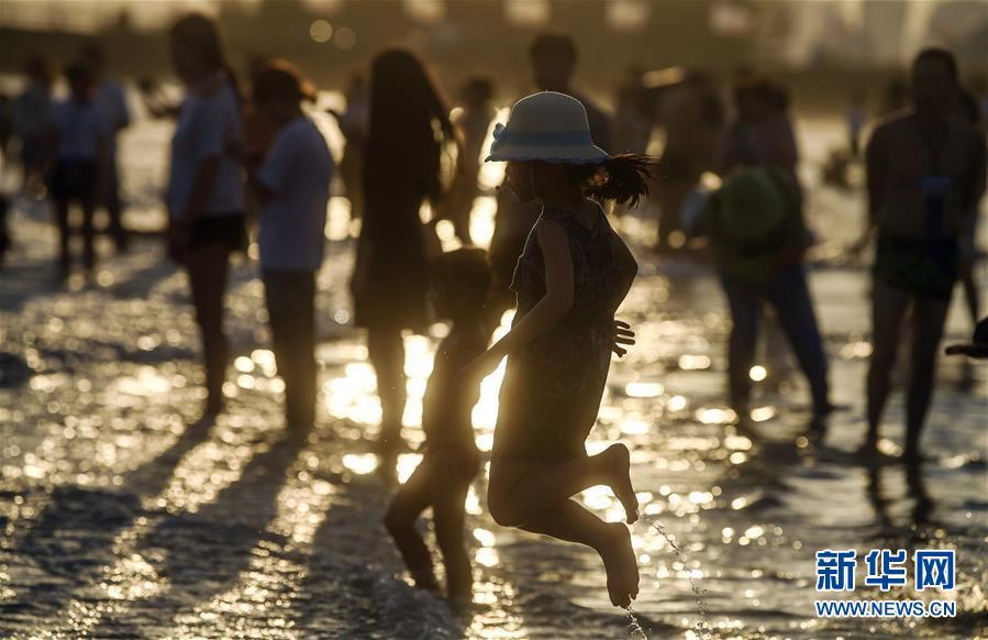 <br/>   6月25日,游客在广西北海市银滩游玩。 近日,广西北海市银滩进入旅游旺季。 新华社记者 刘莲芬 摄