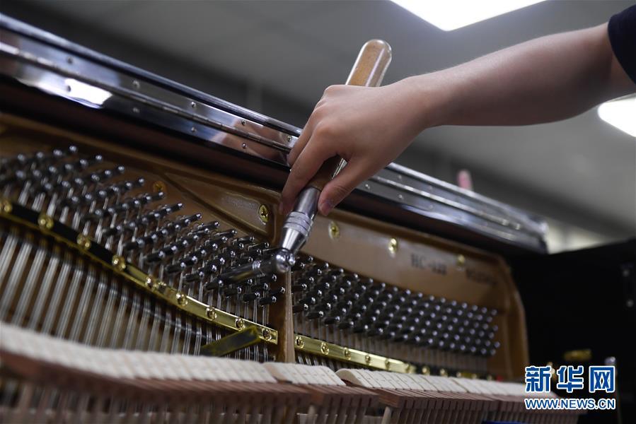 7월 4일 더칭(德淸)현 뤄서(洛舍)진의 한 피아노 공장, 현지 직원이 피아노 음을 조율하고 있다. [사진 출처: 신화망]<br/>