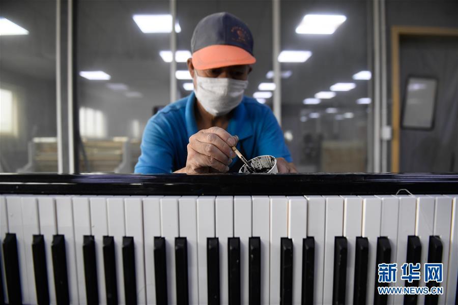 7월 4일 더칭(德淸)현 뤄서(洛舍)진의 한 피아노 공장, 현지 직원이 피아노 도색을 하고 있다. [사진 출처: 신화망]