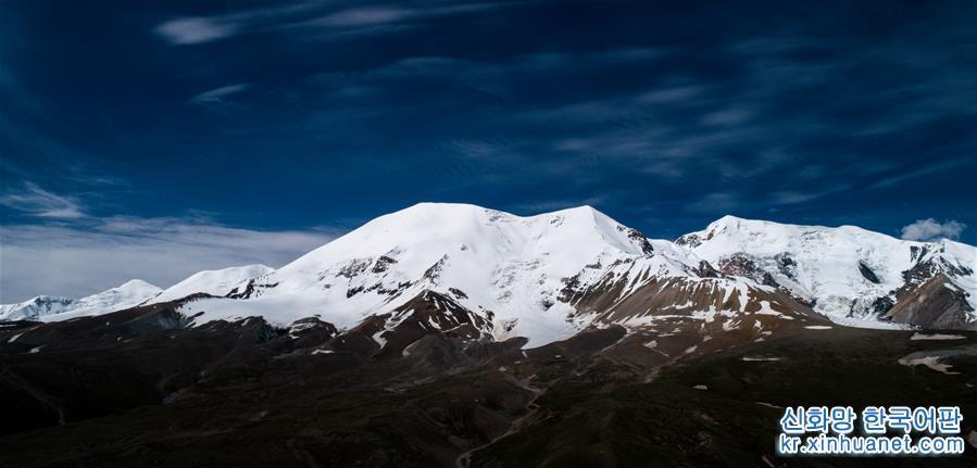 7월10일 드론으로 촬영한 눈덮인 아니마칭산 장관. 칭하이성 궈뤄(果洛) 짱족자치주 마친(瑪沁)현 경내에 위치한 아니마칭(阿尼瑪卿) 설산은 황하 발원지의 최대 산봉우리다. 아니마칭산의 주봉은 6282m이며, 5000m가 넘는 산봉우리가 18개 있고, 1년 내내 운무로 자욱해 &lsquo;황하 유역의 산중 제왕&rsquo;으로 불린다. 여름이 되면서 아니마칭 설산 주위에는 푸른 풀과 만발한 꽃들로 장관을 이룬다. 맑은 날씨에 성스러운 설산과 푸른 하늘, 흰구름이 어우러진 모습은 매혹적인 풍경을 연출한다. [촬영/신화사 기자 우강(吳剛)]<br/>