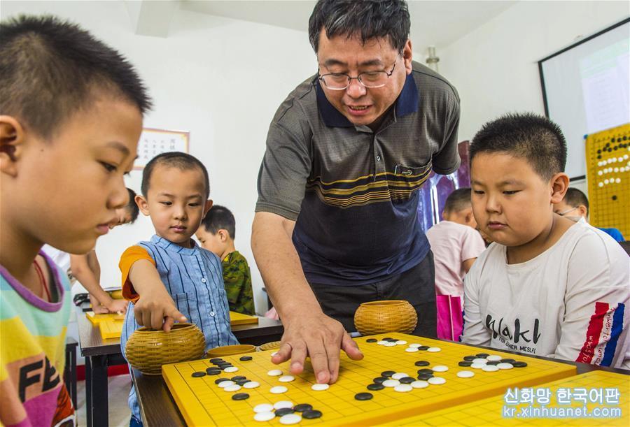 7월11일, 허베이성 자오창(棗強)현 청소년 활동센터에서 초등학생들이 바둑을 배우고 있다. 허베이성 자오창현은 여름방학을 맞아 미성년자들을 위한 건강한 성장 무대를 만들고 각종 문화스포츠 활동을 개설해 어린이들이 즐거운 분위기 속에서 건강하고 알찬 여름방학을 보내도록 하고 있다. [촬영/신화사 기자 리샤오궈(李曉果)]<br/>