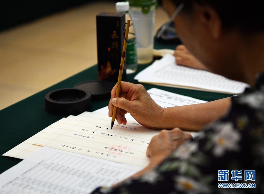 7월 16일 왕수신(王書欣) 전 산시사범대학(陜西師範大學) 교수가 서예 입학통지서를 쓰고 있다.<br/>