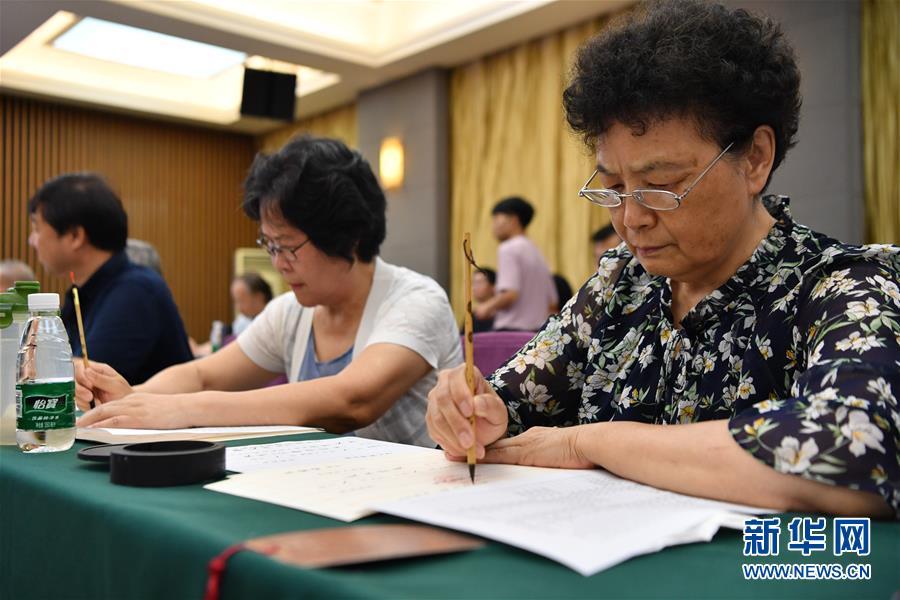 7월 16일 왕수신(王書欣•오른쪽 1번째) 전 산시사범대학(陜西師範大學) 교수가 서예 입학통지서를 쓰고 있다.