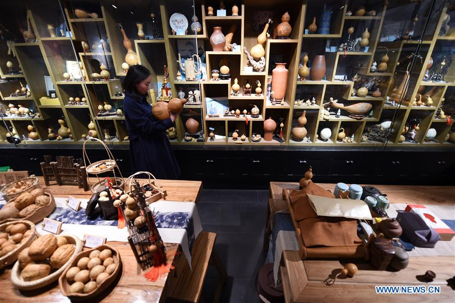<br/> Ruan Xiyue, the fourth generation artist of Carved Gourd Ruan, arranges the handicrafts at a gourd carving studio in Lanzhou, northwest China's Gansu Province, April 1, 2019. A carved gourd, as the name suggests, is a gourd carved with landscapes, portraits, animals, calligraphy or poems, and then painted with ink. The process of gourd carving includes choosing gourd, painting, engraving and coloring. It was inscrbed in the first group of provincial intangible cultural heritages of Gansu in 2006. (Xinhua/Fan Peishen)<br/>