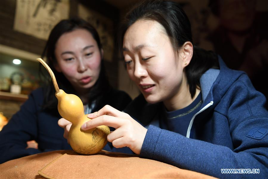 Ruan Xiyue (L), the fourth generation artist of Carved Gourd Ruan, communicates with Ruan Yizhou, an arts and crafts master of Gansu Province, at a gourd carving studio in Lanzhou, northwest China's Gansu Province, April 1, 2019. A carved gourd, as the name suggests, is a gourd carved with landscapes, portraits, animals, calligraphy or poems, and then painted with ink. The process of gourd carving includes choosing gourd, painting, engraving and coloring. It was inscrbed in the first group of provincial intangible cultural heritages of Gansu in 2006. (Xinhua/Fan Peishen)<br/>