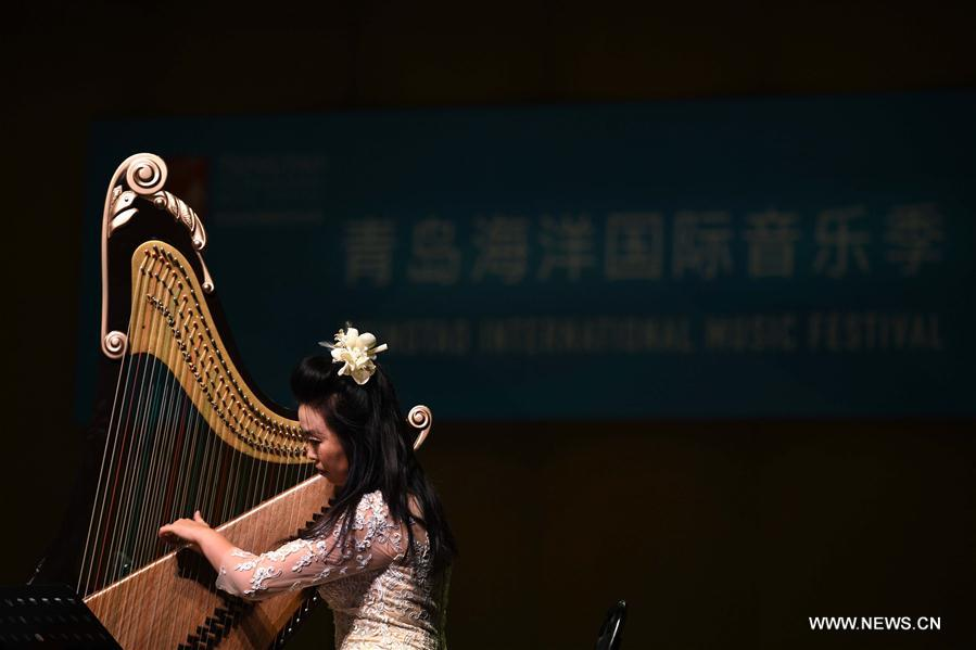 """<br/> A harp musician performs at a traditional Chinese music concert themed on """"Lofty Mountains and Flowing Water"""" held as a part of the first Tsingtao International Music Festival in Qingdao, east China's Shandong Province, Aug. 4, 2019. (Xinhua/Li Ziheng)<br/>"""