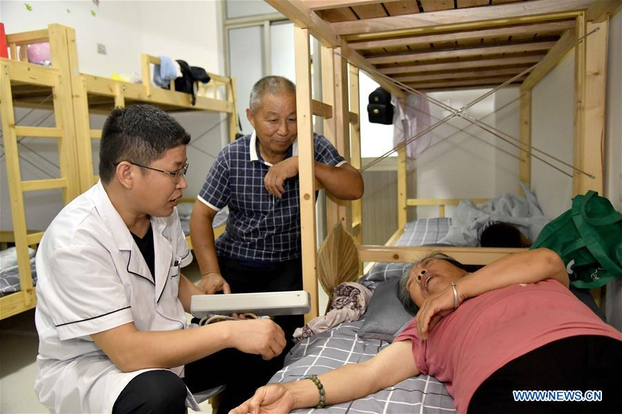 <br/>A resident receives medical treatment at a middle school, which now serves as a relocation site, in Shouguang, east China's Shandong Province, Aug. 12, 2019. About 93,000 local residents have been relocated as Typhoon Lekima wreaked havoc in parts of Shouguang. (Xinhua/Guo Xulei)<br/>