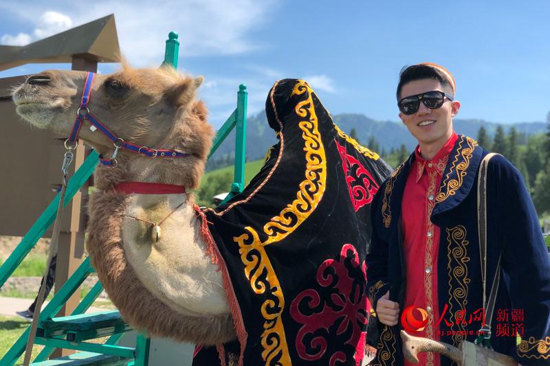 카자흐족(哈薩克族) 전통의상을 입은 인민망 기자가 나라티(那拉提)초원에서 낙타와 기념사진을 찍는 모습 [사진 출처: 인민망]<br/>