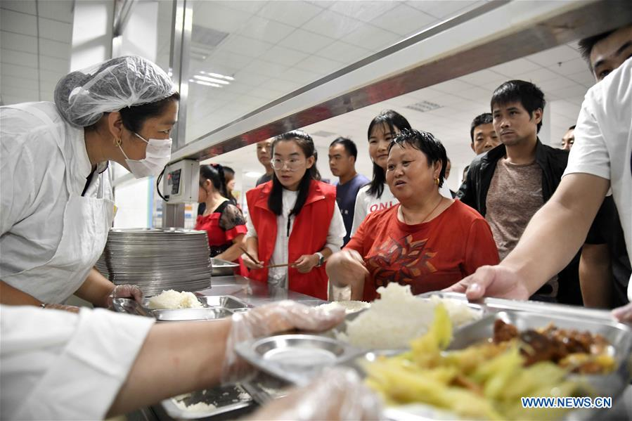 People get meals at a middle school, which now serves as a relocation site, in Shouguang, east China's Shandong Province, Aug. 12, 2019. About 93,000 local residents have been relocated as Typhoon Lekima wreaked havoc in parts of Shouguang. (Xinhua/Guo Xulei)<br/>