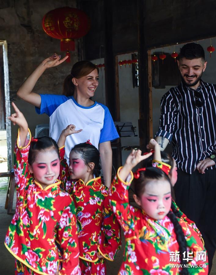 """9月11日,外国友人跟着小浦镇当地幼儿园""""小京迷""""表演队的孩子们学演京剧。 新华社记者 徐昱 摄"""