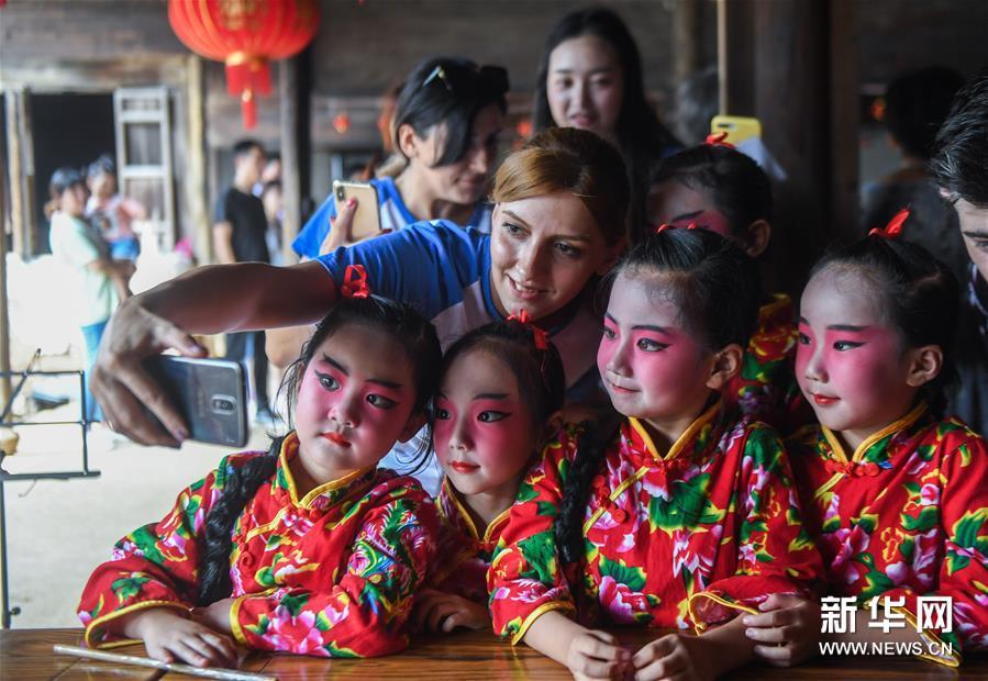 9月11日,来自亚美尼亚的扎娜(左上)与小浦镇当地幼儿园&ldquo;小京迷&rdquo;表演队的孩子们合影。 新华社记者 徐昱 摄<br/>