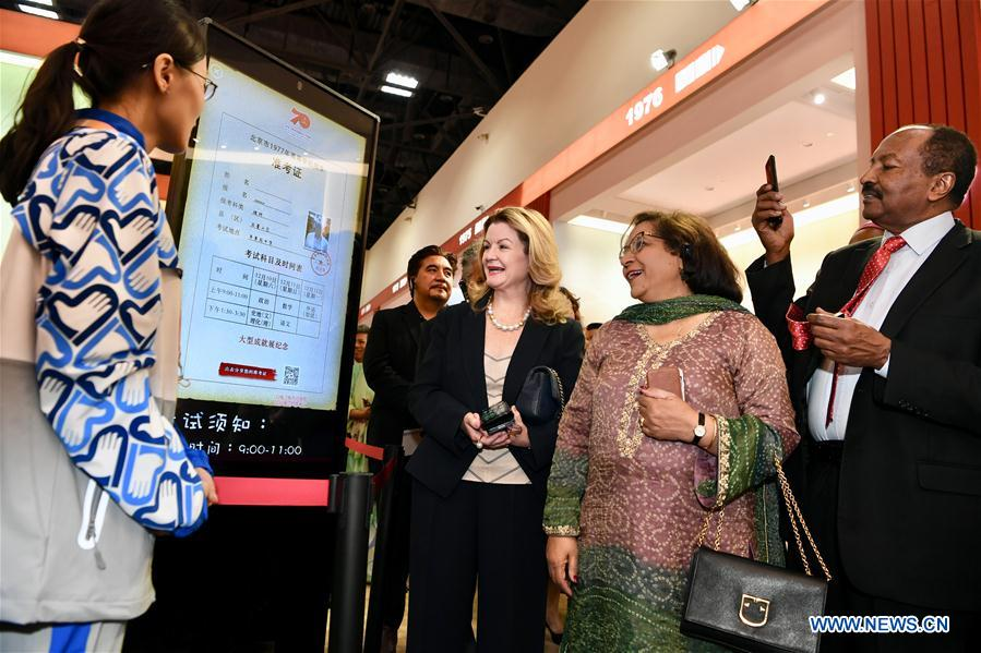 Foreign ambassadors, diplomats and guests view an interact display showing China's national college entrance examination in 1977 at a grand exhibition of achievements in commemoration of the 70th anniversary of the founding of the People's Republic of China (PRC) at the Beijing Exhibition Center in Beijing, capital of China, Sept. 25, 2019. (Xinhua/Jiang Kehong)<br/>