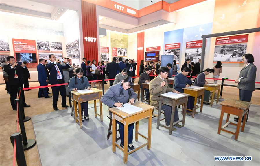 <br/> Oversea Chinese view a scene of China's national college entrance examination in 1977 at a grand exhibition of achievements in commemoration of the 70th anniversary of the founding of the People's Republic of China (PRC) at the Beijing Exhibition Center in Beijing, capital of China, Sept. 28, 2019. Some 2,000 oversea Chinese were invited to visit the exhibition on Saturday. (Xinhua/Chen Yehua)<br/>