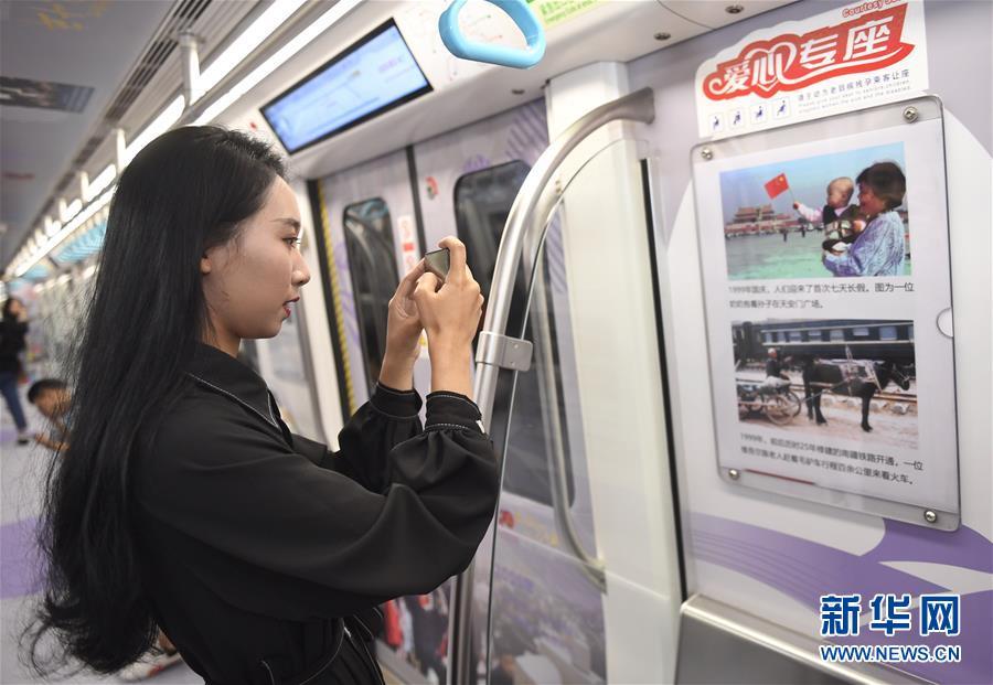 &lsquo;이동 박물관&rsquo; 열차에 전시된 사진을 찍은 승객 [9월 18일 촬영/사진 출처: 신화망]<br/>