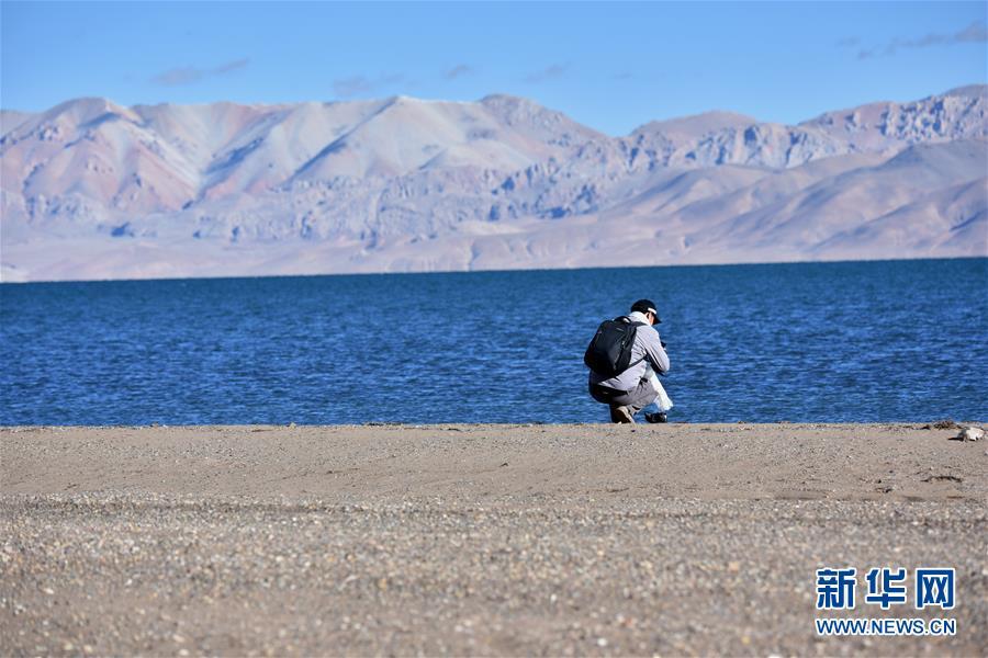 <br/>  西藏那曲市申扎县格仁错湖旁的游客(10月12日摄)。 深秋时节的藏北,最低气温已降至零摄氏度以下,呈现出苍凉和壮美交织的独特景观。 新华社记者 周锦帅 摄