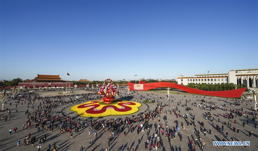 Tourists view the basket-shaped flower parterre at Tian'anmen Square in Beijing, capital of China, Oct. 14, 2019. (Xinhua/Yin Gang)<br/>