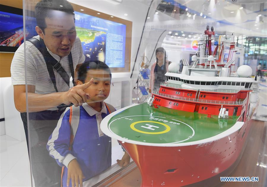 """Visitors look at a model of the deep-water engineering vessel at the booth of the China National Offshore Oil Corporation at the 2019 China Marine Economy Expo in Shenzhen, south China's Guangdong Province, Oct. 15, 2019. The expo, under the theme of """"Sharing Blue Economy Opportunities, Building a Shared Future,"""" opened here on Tuesday. It has attracted more than 450 companies and institutions to participate and is expected to present China's achievements in the marine economy and the latest progress in the global marine industry. (Xinhua/Mao Siqian)<br/>"""