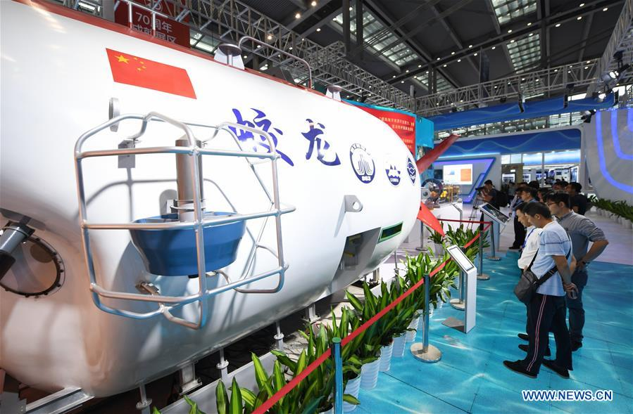 """Visitors look at the model of the China's manned submersible Jiaolong at the 2019 China Marine Economy Expo in Shenzhen, south China's Guangdong Province, Oct. 15, 2019. The expo, under the theme of """"Sharing Blue Economy Opportunities, Building a Shared Future,"""" opened here on Tuesday. It has attracted more than 450 companies and institutions to participate and is expected to present China's achievements in the marine economy and the latest progress in the global marine industry. (Xinhua/Mao Siqian)<br/>"""