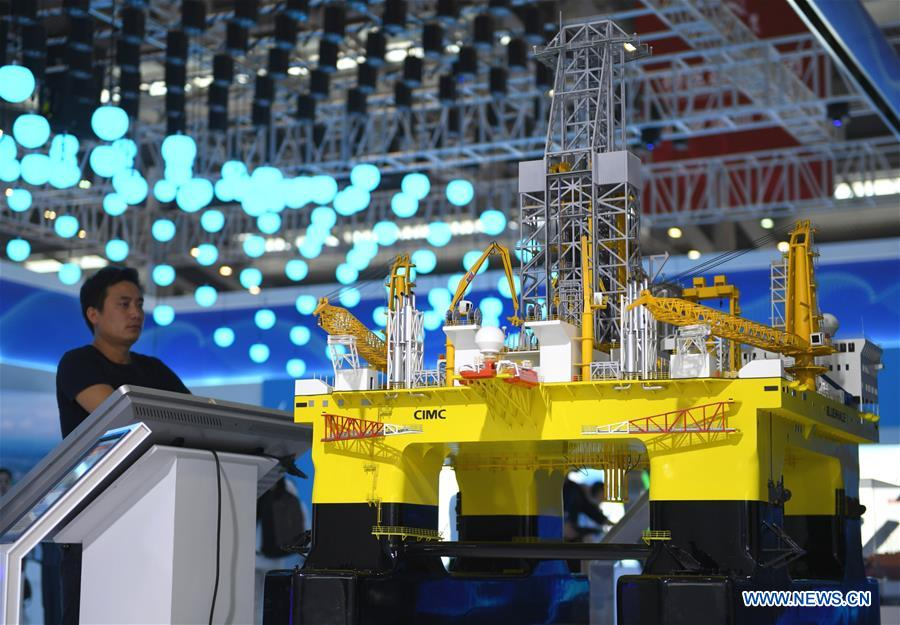 """A visitor looks at the model of an oil rig at the 2019 China Marine Economy Expo in Shenzhen, south China's Guangdong Province, Oct. 15, 2019. The expo, under the theme of """"Sharing Blue Economy Opportunities, Building a Shared Future,"""" opened here on Tuesday. It has attracted more than 450 companies and institutions to participate and is expected to present China's achievements in the marine economy and the latest progress in the global marine industry. (Xinhua/Mao Siqian)"""