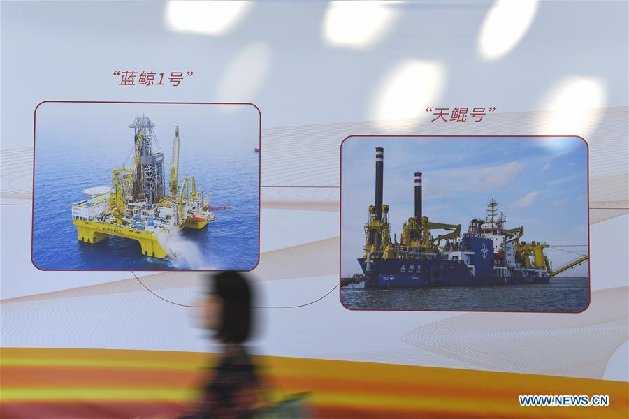 """A visitor walks past a board showcasing an oil rig and a cutter suction dredger at the 2019 China Marine Economy Expo in Shenzhen, south China's Guangdong Province, Oct. 15, 2019. The expo, under the theme of """"Sharing Blue Economy Opportunities, Building a Shared Future,"""" opened here on Tuesday. It has attracted more than 450 companies and institutions to participate and is expected to present China's achievements in the marine economy and the latest progress in the global marine industry. (Xinhua/Mao Siqian)<br/>"""