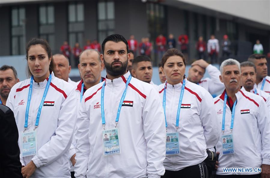 Members of the Syria delegation participate in the flag-raising ceremony at the athletes' village of the 7th International Military Sports Council (CISM) Military World Games in Wuhan, capital of central China's Hubei Province, Oct. 16, 2019.(Xinhua/Wan Xiang)<br/>
