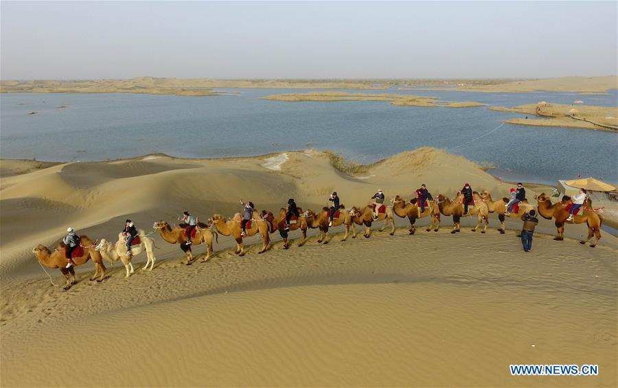 Photo taken on Oct. 26, 2019 shows tourists riding camels to enjoy the desert scenery at Lop Nur People Village in Yuli County, northwest China's Xinjiang Uygur Autonomous Region. In the first three quarters of this year, Xinjiang received over 183.85 million tourists from home and abroad with a year-on-year increase of 40.9 percent, and saw a total tourism revenue of more than 304.6 billion yuan (about 43.1 billion U.S. dollars) with a year-on-year growth of 40.78 percent. (Xinhua/Zhao Ge)<br/>