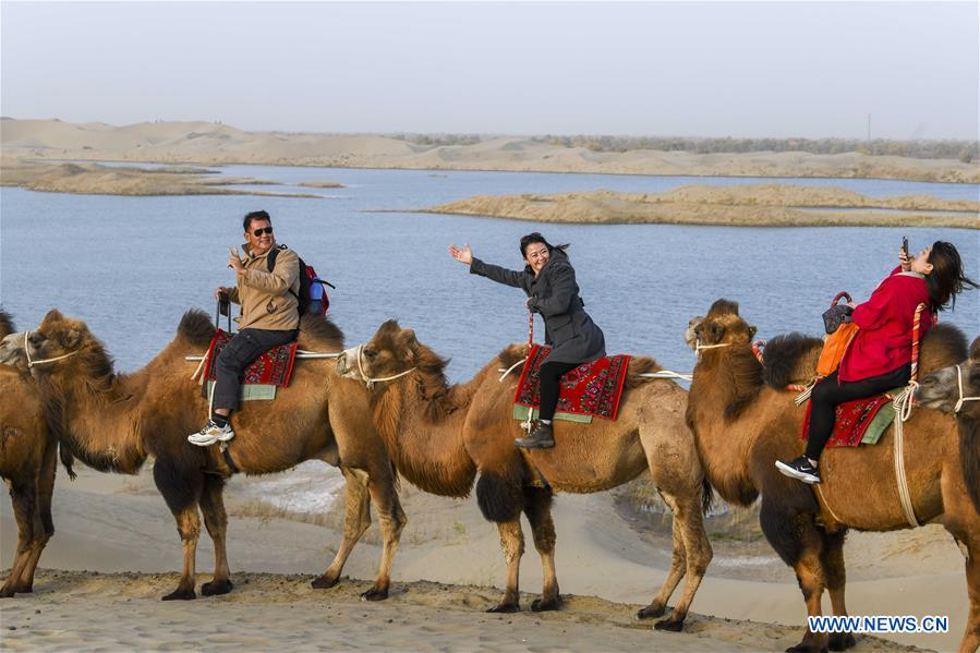 Tourists riding camels take photos beside the Shennyu Lake at Lop Nur People Village in Yuli County, northwest China's Xinjiang Uygur Autonomous Region, Oct. 26, 2019. In the first three quarters of this year, Xinjiang received over 183.85 million tourists from home and abroad with a year-on-year increase of 40.9 percent, and saw a total tourism revenue of more than 304.6 billion yuan (about 43.1 billion U.S. dollars) with a year-on-year growth of 40.78 percent. (Xinhua/Zhao Ge)<br/>