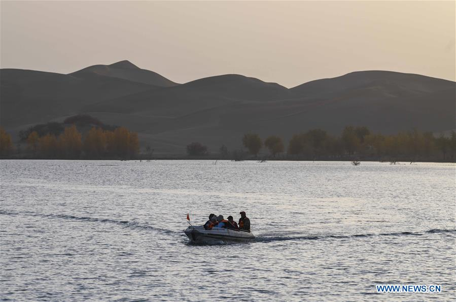 Tourists take a boat at Lop Nur in Yuli County, northwest China's Xinjiang Uygur Autonomous Region, Oct. 25, 2019. In the first three quarters of this year, Xinjiang received over 183.85 million tourists from home and abroad with a year-on-year increase of 40.9 percent, and saw a total tourism revenue of more than 304.6 billion yuan (about 43.1 billion U.S. dollars) with a year-on-year growth of 40.78 percent. (Xinhua/Zhao Ge)<br/>