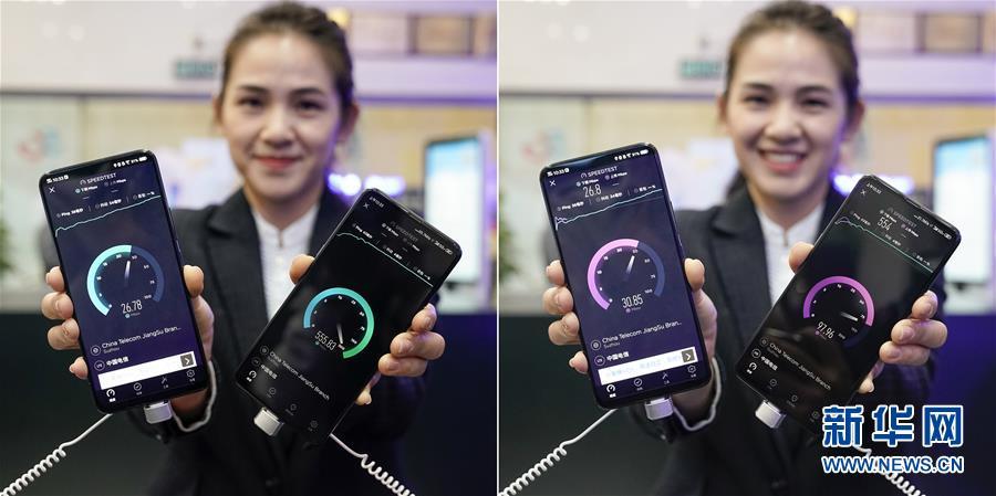 차이나텔레콤 영업점 직원이 차이나텔레콤의 5G 서비스와 4G 서비스의 실시간 다운로드 속도(왼쪽)와 업로드 속도(오른쪽) 테스트 결과를 보여주고 있다. [10월 31일 촬영/사진 출처: 신화망]