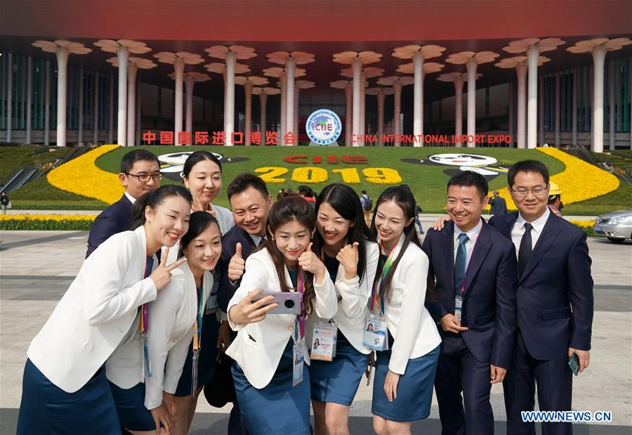 Staff members pose for a group photo at the south square of the National Exhibition and Convention Center (Shanghai), a main venue for the second China International Import Expo (CIIE), in Shanghai, east China, Nov. 4, 2019. The second CIIE is scheduled to run from Nov. 5 to Nov. 10 in Shanghai. (Xinhua/Yin Gang)<br/>