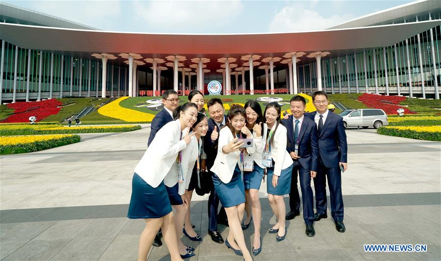 Staff members pose for a group photo at the south square of the National Exhibition and Convention Center (Shanghai), a main venue for the second China International Import Expo (CIIE), in Shanghai, east China, Nov. 4, 2019. The second CIIE is scheduled to run from Nov. 5 to Nov. 10 in Shanghai. (Xinhua/Chen Jianli)<br/>