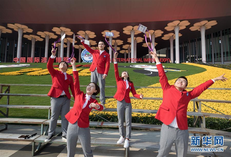 11月10日,第二届进博会志愿者在上海国家会展中心场馆入口处留影。 在上海国家会展中心举行的第二届中国国际进口博览会10日闭幕。 新华社记者 金立旺 摄<br/>