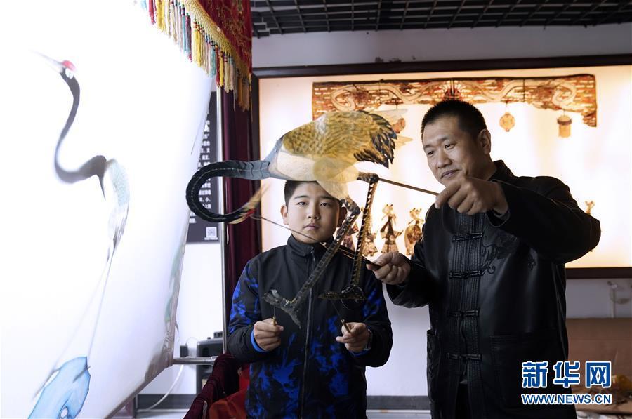 11월 10일 궈바오(郭宝•오른쪽) 씨는 피잉(皮影) 전승관에서 아이들에게 피잉을 가르치고 있다. [사진 출처: 신화망]