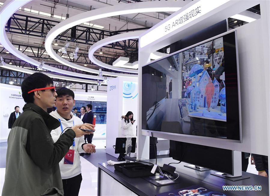 "A staff member (R) guides a visitor experience AR technology at the 2019 World 5G Convention in Beijing, capital of China, Nov. 21, 2019. Themed ""5G changes the world, 5G creates the future,"" the 2019 World 5G Convention kicked off Thursday in Beijing. (Xinhua/Ren Chao)<br/>"