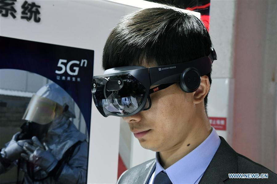 "A staff member displays a Mixed Reality (MR) terminal device at the 2019 World 5G Convention in Beijing, capital of China, Nov. 21, 2019. Themed ""5G changes the world, 5G creates the future,"" the 2019 World 5G Convention kicked off Thursday in Beijing. (Xinhua/Ren Chao)<br/>"