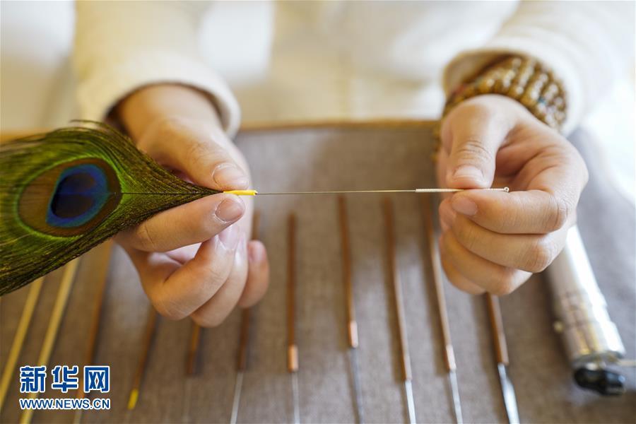 지난 5일 차이얼 전문가 리춘린이 그녀의 차이얼 도구를 살펴보고 있다. [사진 출처: 신화망]<br/>