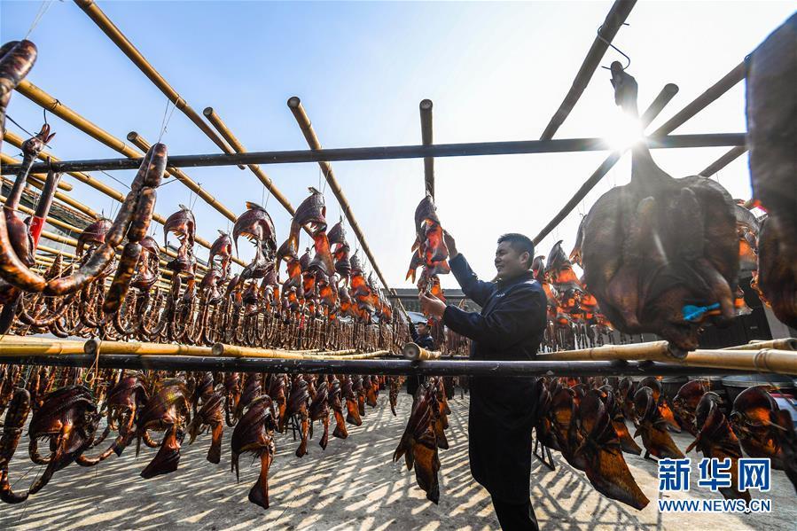 12월 3일 안창고진의 소세지 전통상점 직원이 각종 수공법으로 건어육 특산품을 말리고 있다. [사진 출처: 신화망]