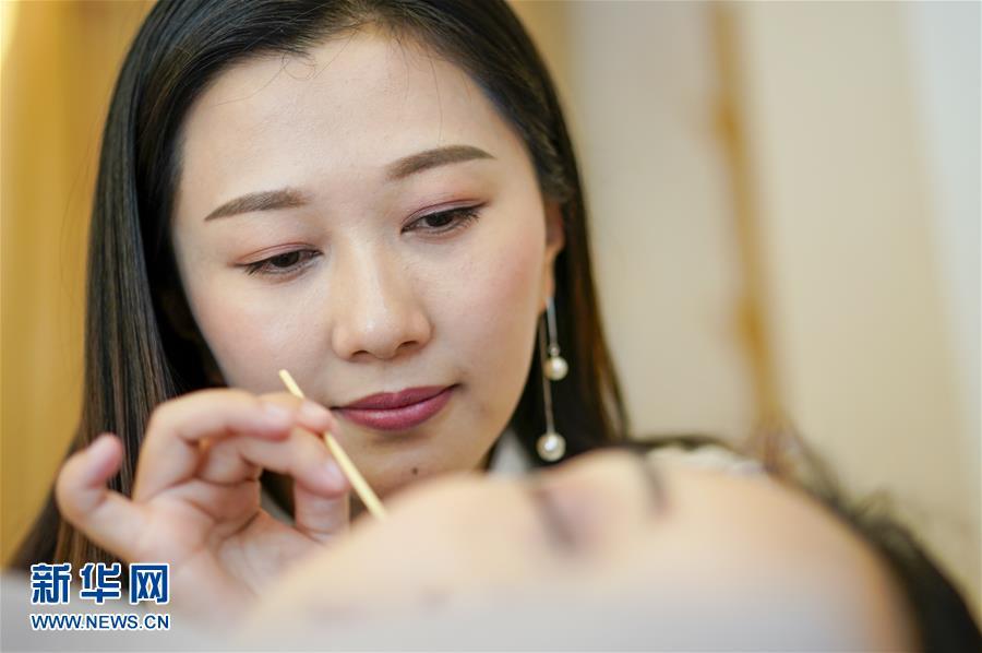 지난 5일 차이얼 전문가 리춘린이 충칭 촨얼장비물질문화유산차이얼훈련소에서 고객들에게 차이얼 서비스를 제공하고 있다. [사진 출처: 신화망]<br/>