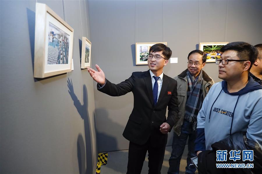 북경이공대학에 재학 중인 조선 유학생 김일범(왼쪽)이 봉사자로서 전시품을 설명하고 있다. [사진 출처: 신화망]