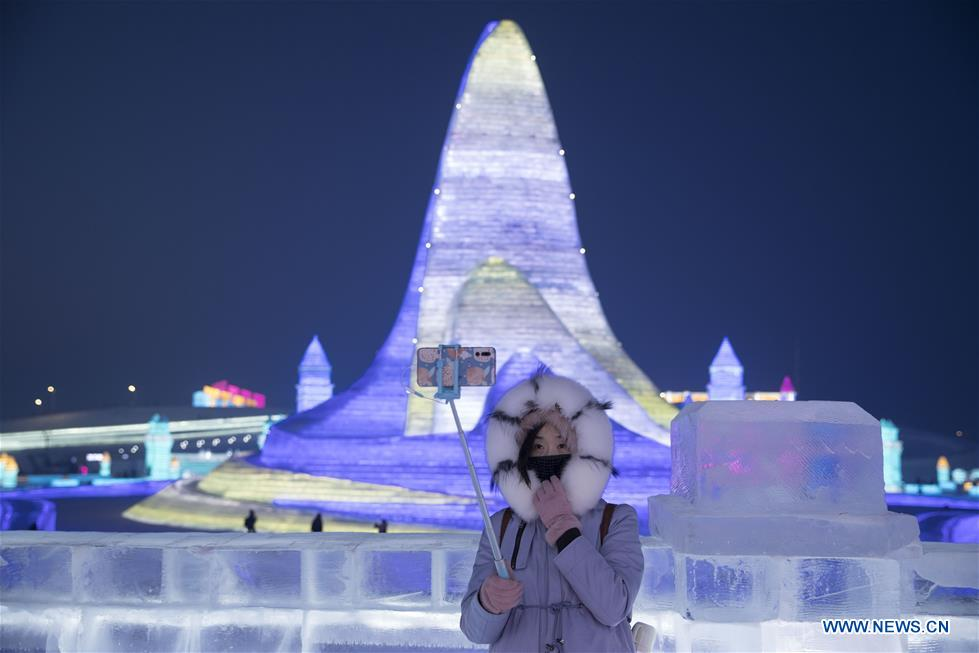 A woman poses for photos during the 21st edition of Ice-Snow World in Harbin, capital of northeast China's Heilongjiang Province, Dec. 23, 2019. (Photo by Zhang Tao/Xinhua)<br/>