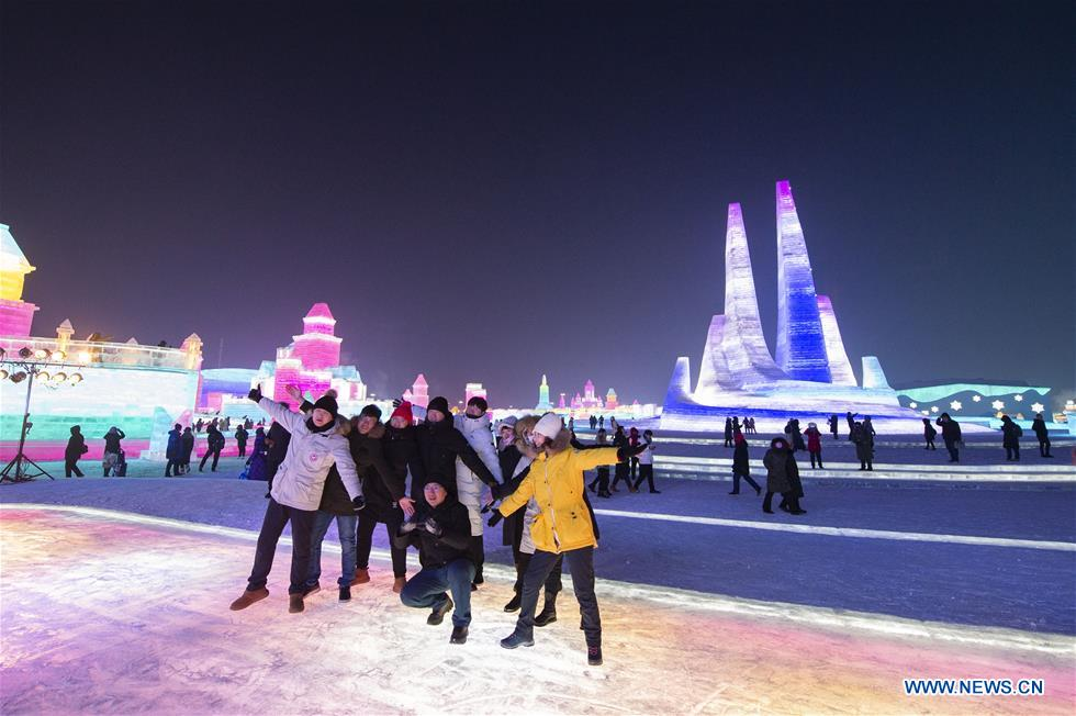People pose for photos during the 21st edition of Ice-Snow World in Harbin, capital of northeast China's Heilongjiang Province, Dec. 23, 2019. (Photo by Xie Jianfei/Xinhua)<br/>