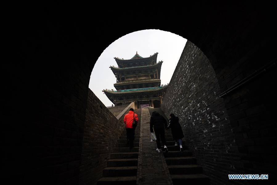 Tourists visit the ancient city of Pingyao in Jinzhong, north China's Shanxi Province, on Dec. 25, 2019. Pingyao, a UNESCO World Cultural Heritage site in north China's Shanxi Province, is famous for its well-preserved ancient architecture including the city walls. The city boomed in the 19th century as China's financial center, as Shanxi merchants expanded their businesses across the country. Now, the well-preserved compounds of these affluent merchants and some emerging modern elements like souvenir shops, bars, photography festival and theatrical performances have again brought the ancient city to life and made it a popular tourist attraction. (Xinhua/Zhan Yan)<br/>