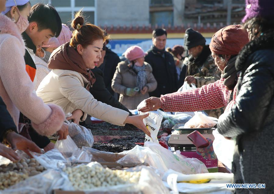 People select goods at a Spring Festival market in Yaofu Township of Pingluo County, northwest China's Ningxia Hui Autonomous Region, Jan. 19, 2020. According to the annals of Yaofu Township, the traditional Spring Festival market here has a history of 79 years. As the Chinese Lunar New Year is approaching, the rich traditional Spring Festival goods and cultural performances in the market attract many people to visit. (Xinhua/Jia Haocheng)<br/>