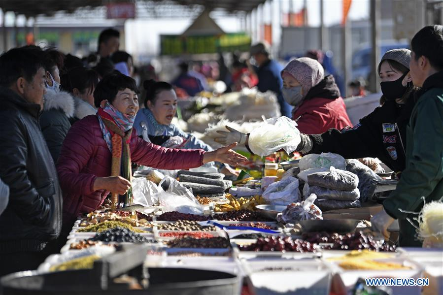 People select goods at a Spring Festival market in Yaofu Township of Pingluo County, northwest China's Ningxia Hui Autonomous Region, Jan. 19, 2020. According to the annals of Yaofu Township, the traditional Spring Festival market here has a history of 79 years. As the Chinese Lunar New Year is approaching, the rich traditional Spring Festival goods and cultural performances in the market attract many people to visit. (Xinhua/Wang Peng)<br/>