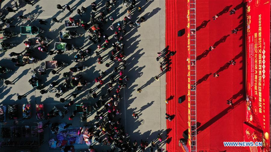 Aerial photo taken on Jan. 19, 2020 shows people watching a show performed by villagers at a Spring Festival market in Yaofu Township of Pingluo County, northwest China's Ningxia Hui Autonomous Region. According to the annals of Yaofu Township, the traditional Spring Festival market here has a history of 79 years. As the Chinese Lunar New Year is approaching, the rich traditional Spring Festival goods and cultural performances in the market attract many people to visit. (Xinhua/Feng Kaihua)<br/>